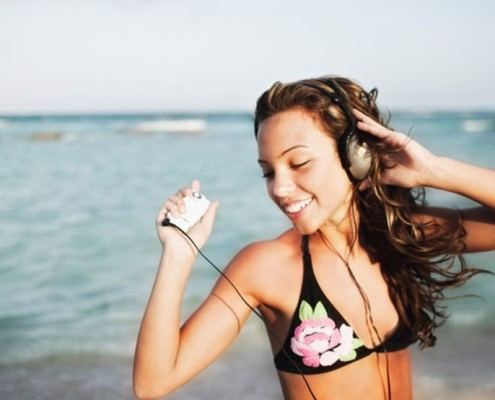 Teenage girl listening to mp3 player at beach
