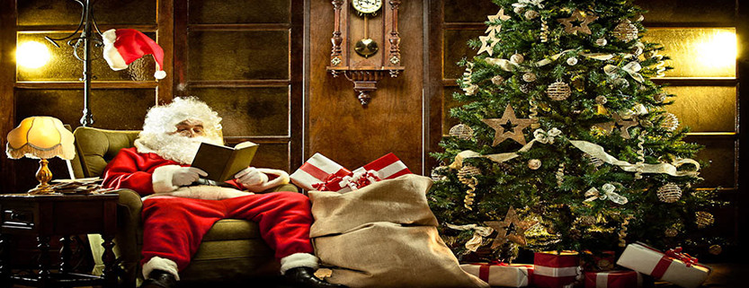 santa claus at home relaxing reading a book near christmas